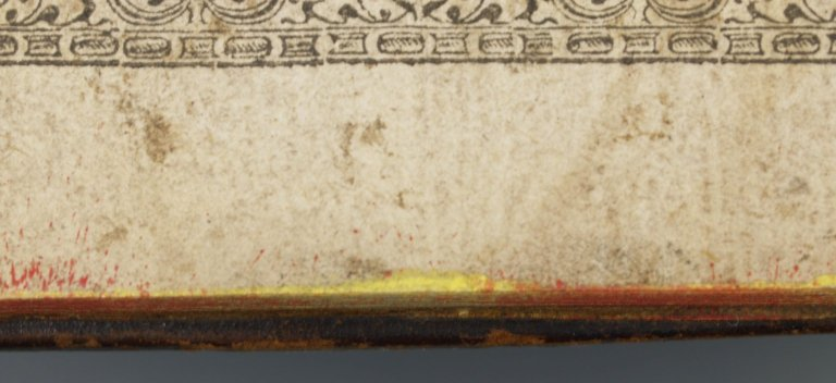 Pastedown, inside the cover (detail), the still-vibrant evidence of yellow and red edge decoration pigment and splatter technique, STC 12908 copy 1.