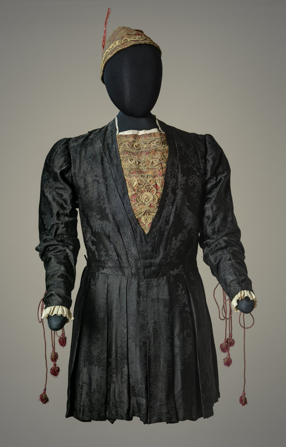 Costume worn by E. H. Sothern in the role of Romeo. Red and green cap with feather Black silk brocade doublet, gold and red brocade insert at neck.